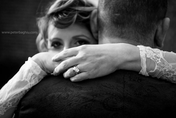Bride looking over groom's shoulder as she hugs him - Picture by Peter Baghiu Photography
