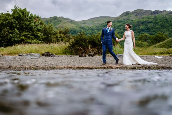 Bride and groom walking holding hands with hills in background - Picture by Cris Lowis Photography