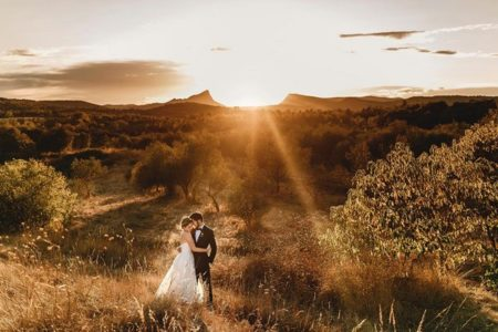 Bride and groom with sun setting in background between two hills - Picture by Andy Gaines Photography