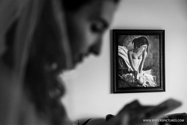 Bride looking at phone with picture of lady on wall in background - Picture by Paul Rogers Photographer