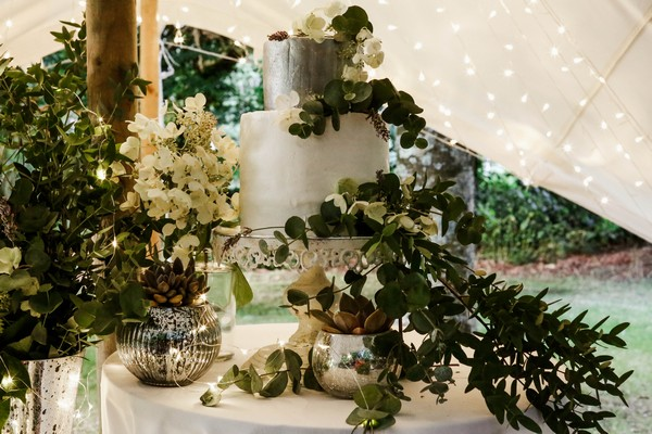 Silver and white wedding cake covered in foliage