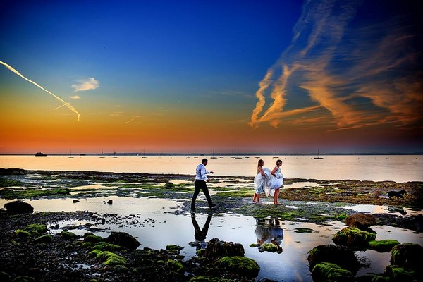 Groom walking across beach towards bride and bridesmaid with beautiful colourful sky - Picture by Marius Tudor Photography