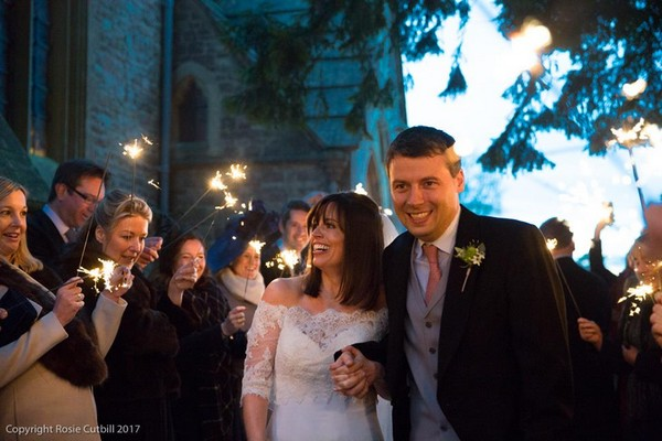 Bride and groom walking holding hands past wedding guests with sparklers - Rosie Cutbill Photography