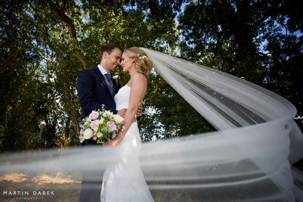 Bride and groom touching heads as bride's veil blows around them - Martin Dabek Photography