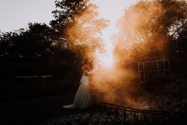 Bride and groom standing as sun shines through mist next to them - Picture by Damian Brandon