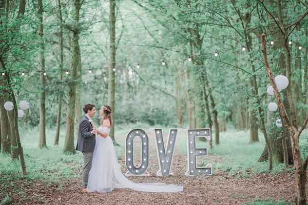 Bride and groom standing by LOVE letters in woodland with bride's dress amking shape of the L - Picture by Ella Parkinson Photography