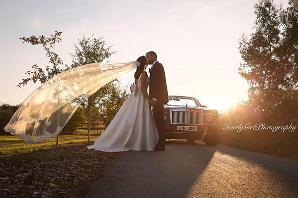 Bride and groom kissing by wedding car with bride's veil blowing in the wind - Picture by Twirly Girl Photography