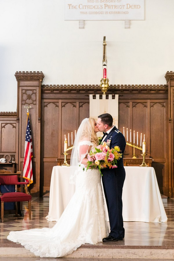 Bride and groom kiss at the altar