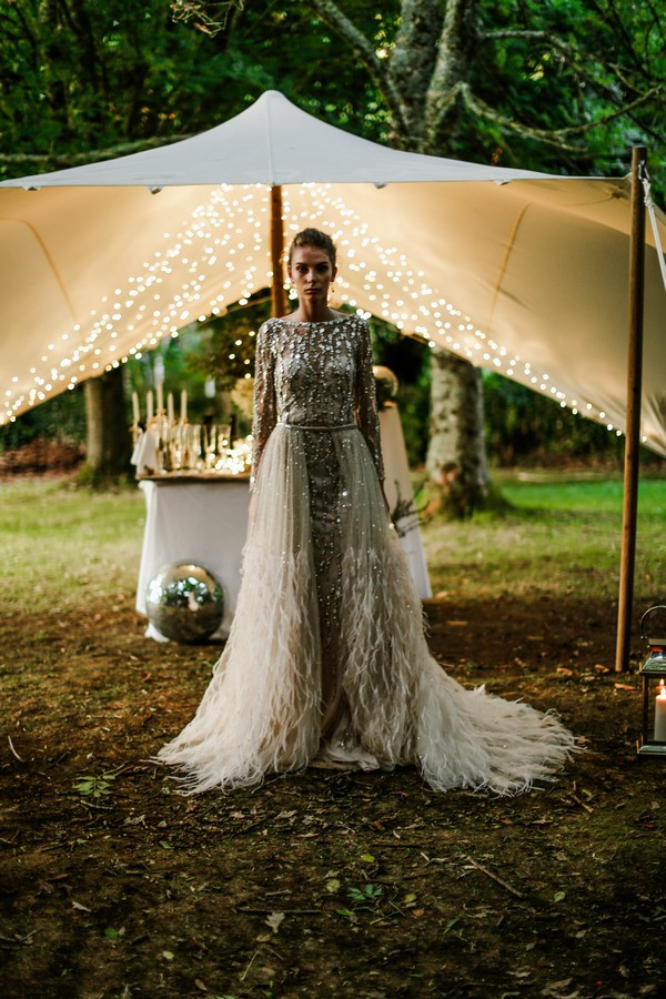 Bride wearing wedding dress with silver detail and feathers