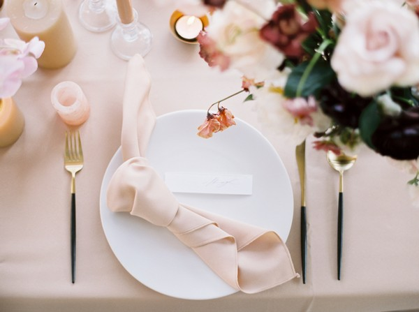 Wedding place setting with tied napkin on plate