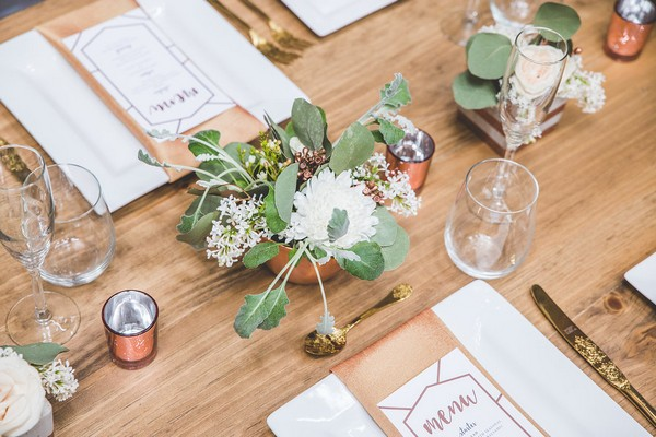 Flowers in copper pot on wooden wedding table