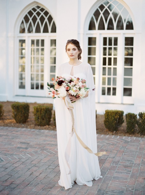 Bride wearing cape holding bouquet