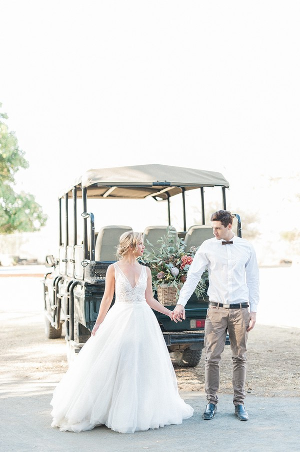 Bride and groom holding hands in front of safari truck