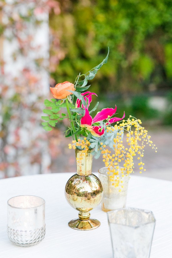 Small gold vase of colourful wedding flowers