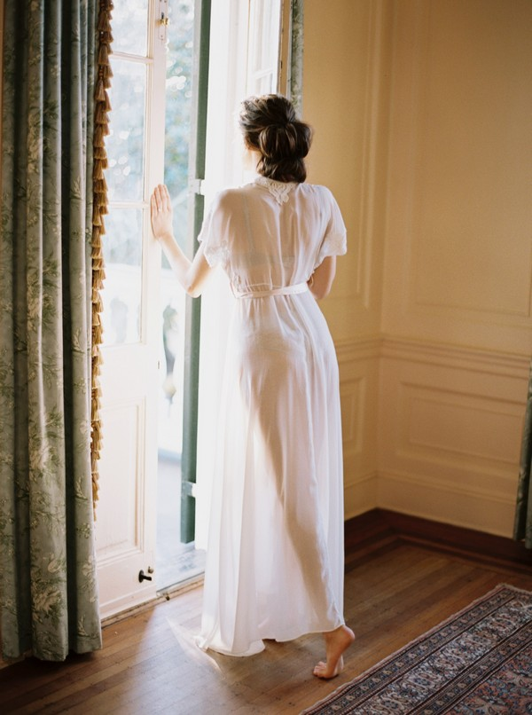 Bride in dressing gown standing by door