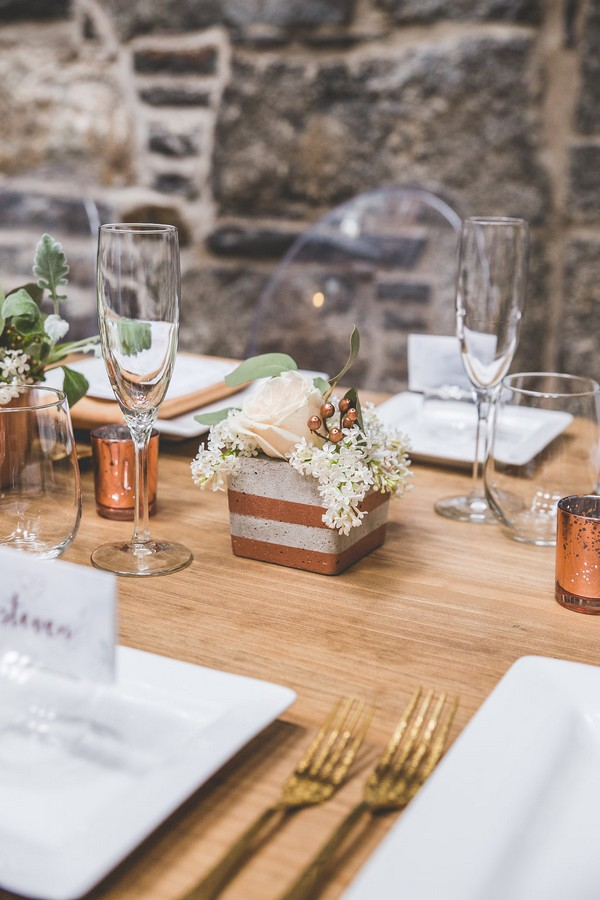 Wedding table flowers in concrete pot with copper stripe