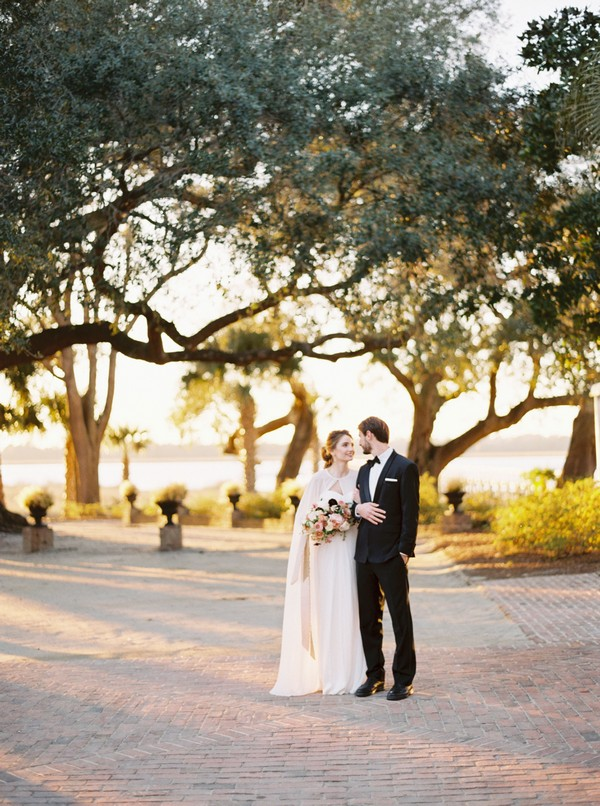 Bride and groom on path in front of trees