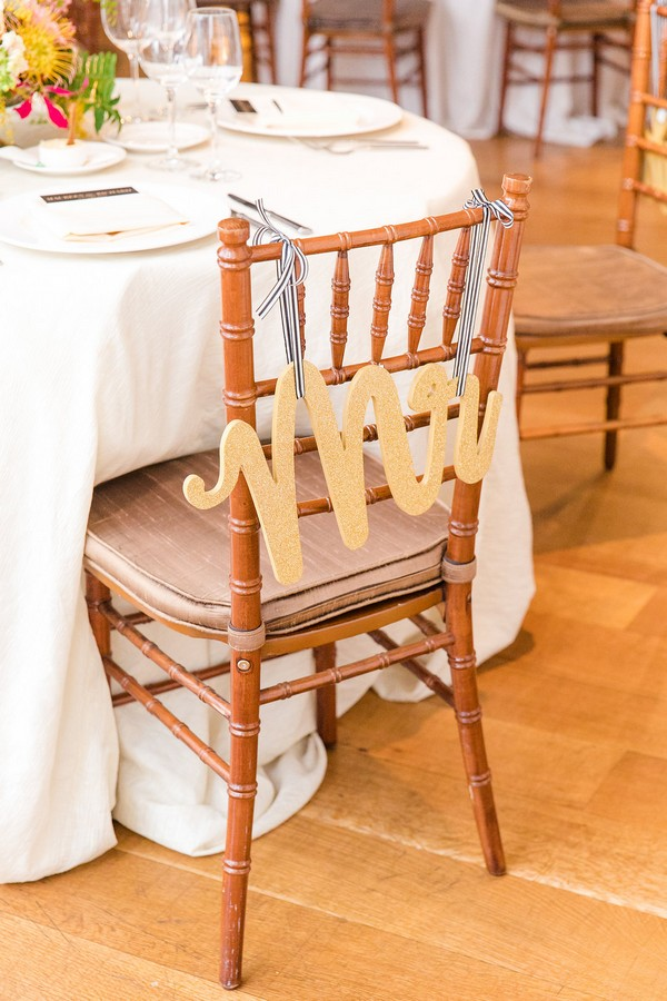 Gold Mr sign hanging from back of wedding chair