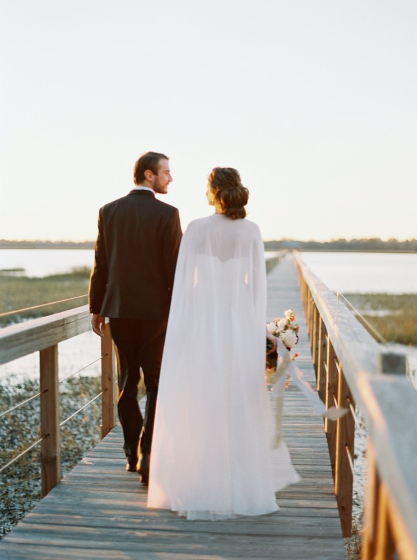 Bride and groom walking over wooden bridge