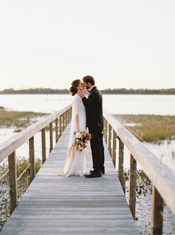 Bride and groom kissing on wooden bridge