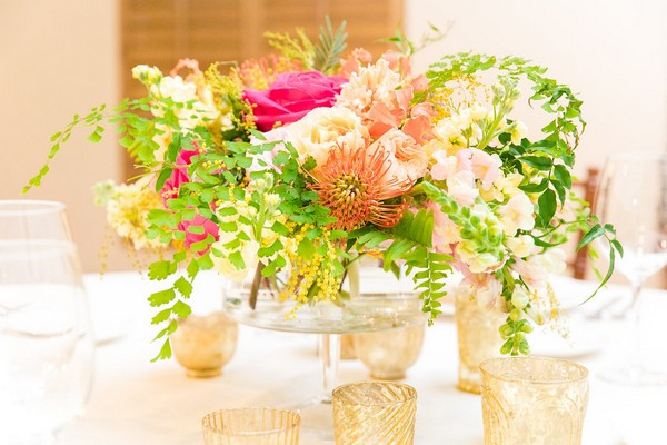 Bright, colourful wedding table flowers with foliage