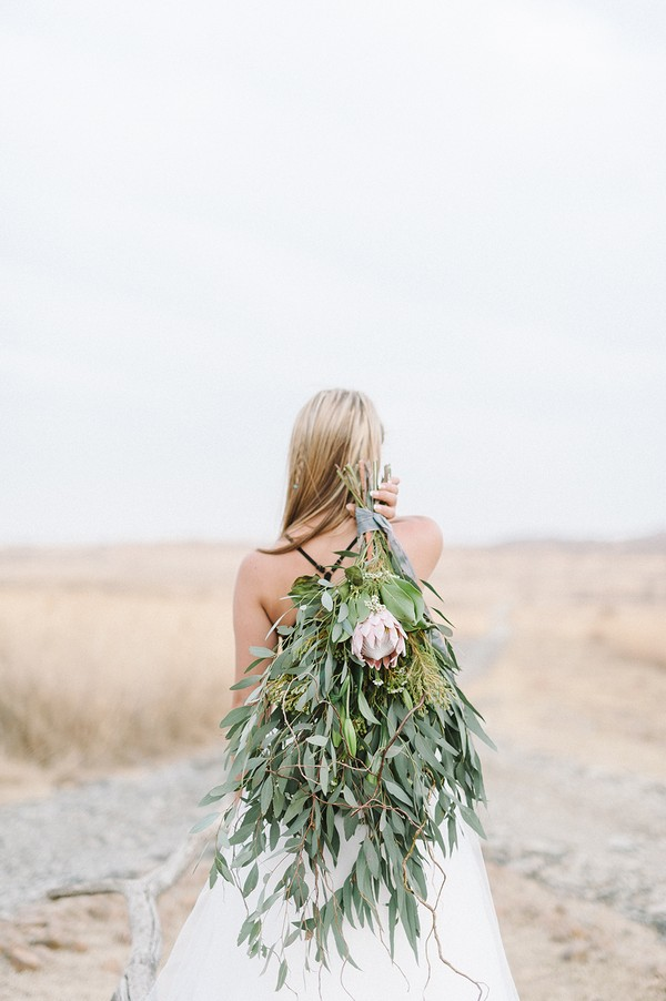 Bride with foliage bouquet over her shoulder