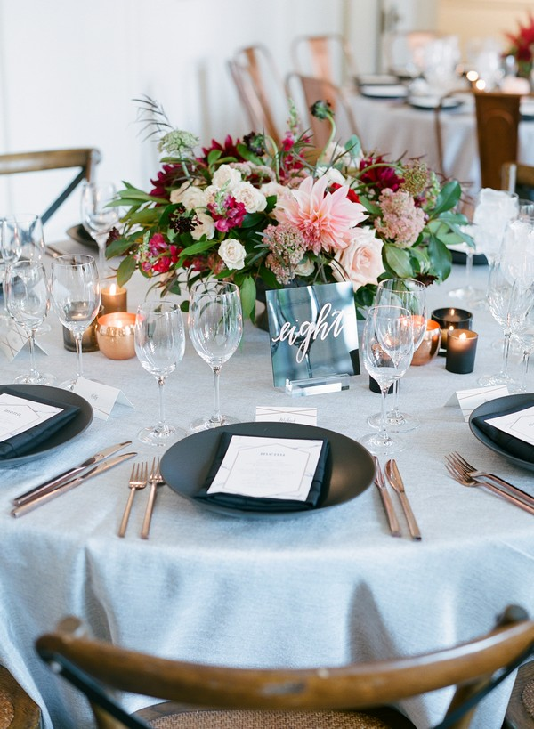 Wedding table with black plates and floral centrepiece
