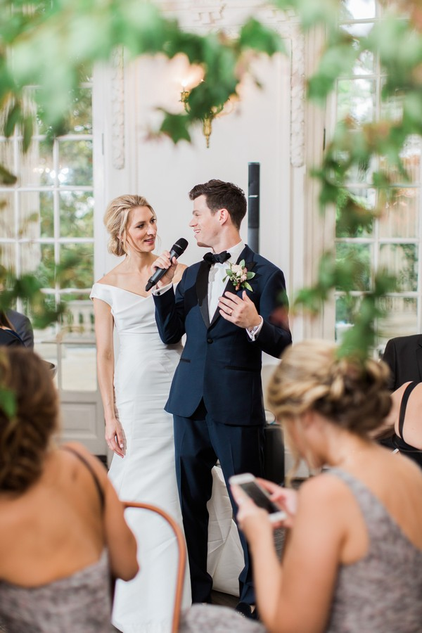Groom giving speech with bride