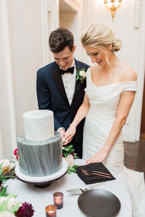 Bride and groom cutting marble effect wedding cake