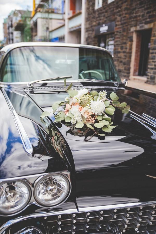 Bridal bouquet on bonnet of Cadillac wedding car