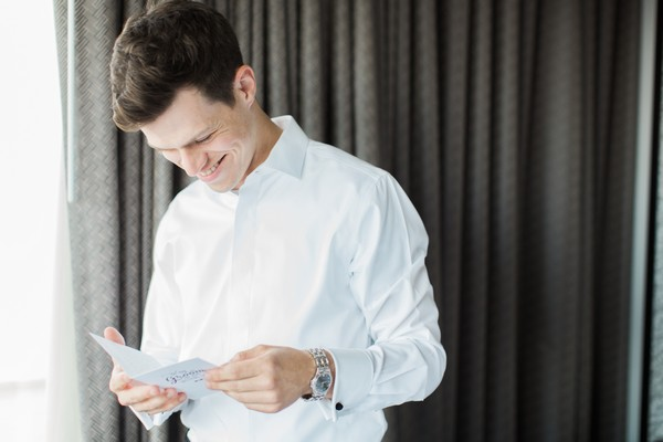 Groom reading note from bride before wedding