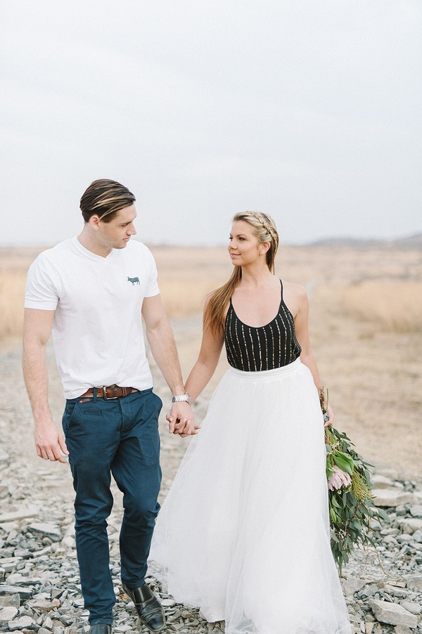 Bride and groom holding hands in South African bush