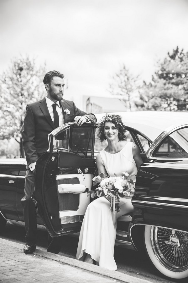 Bride sitting in Cadillac wedding car as groom stands by door
