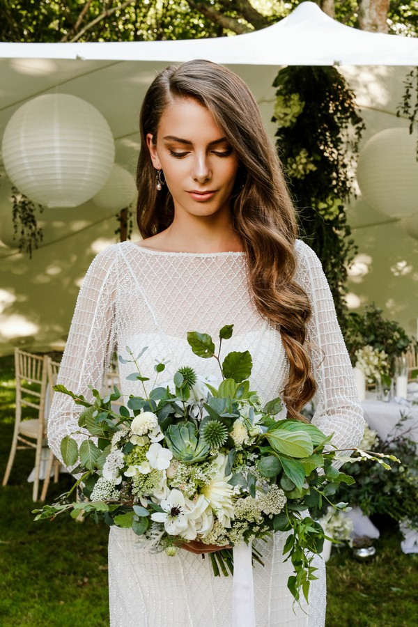 Bride holding bouquet of foliage and white flowers
