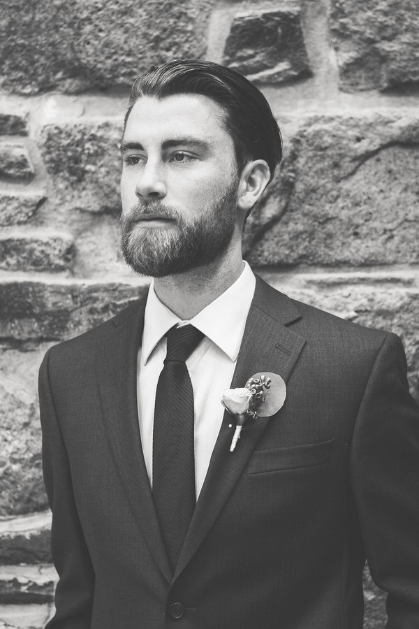 Groom standing up against brick wall