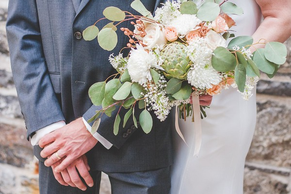 Artichoke, green foliage and white and peach flowers in bride's bouquet