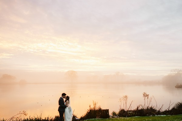 Couple by lake at Sandhole Oak Barn at dusk