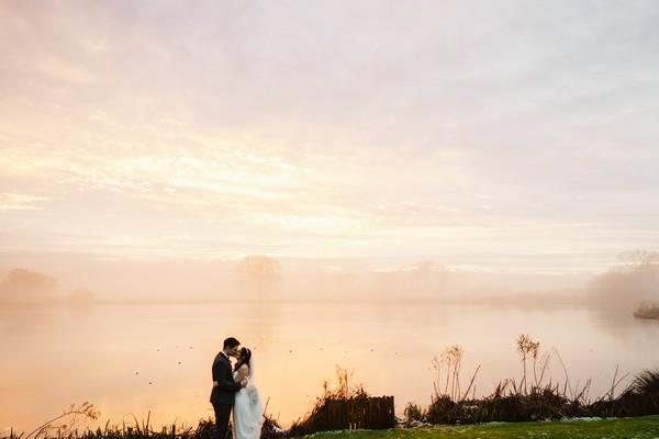 Couple by lake at Sandhole Oak Barn at dusk