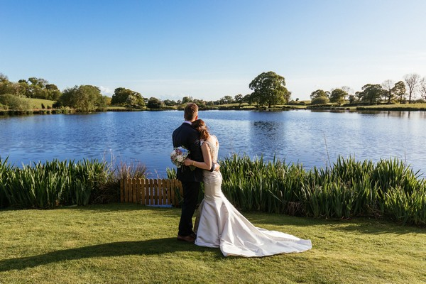 Couple by lake at Sandhole Oak Barn
