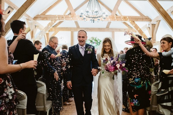 Couple leaving wedding ceremony at Sandhole Oak Barn