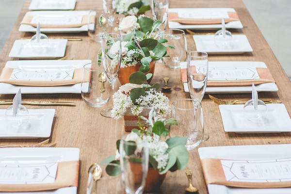 Copper pots of flowers down centre of wooden wedding table
