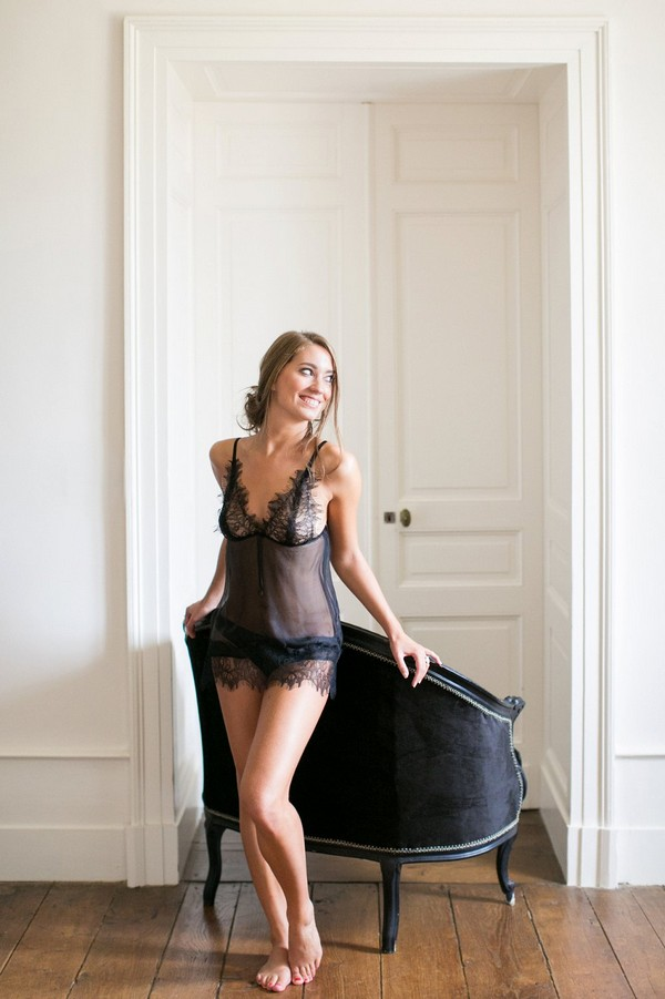 Bride in black lingerie standing by chair