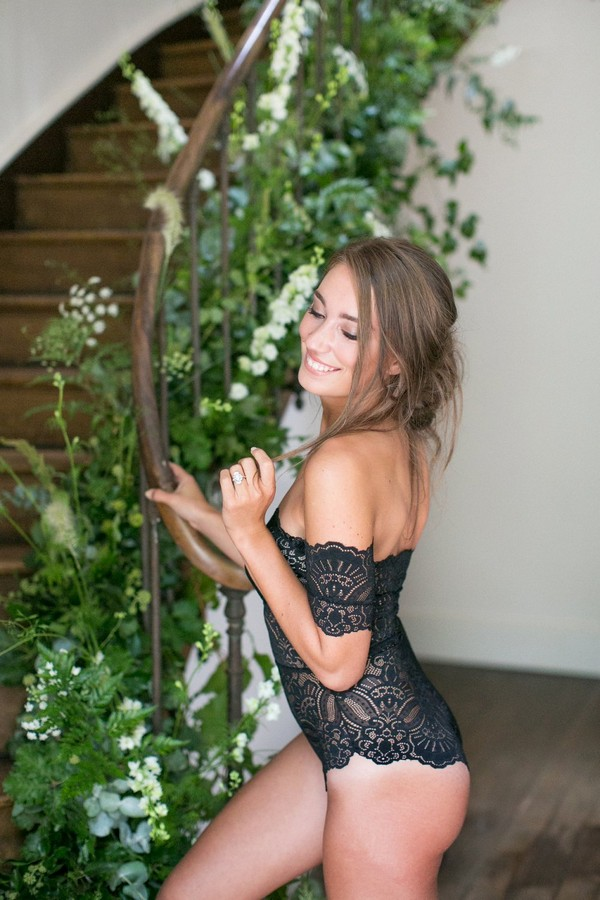 Bride in black lingerie standing by staircase decorated with foliage