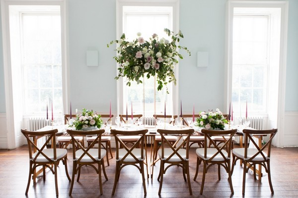 Wooden wedding table and chairs with tall table flowers
