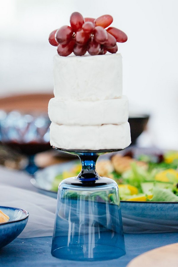 Cheese topped with grapes on upturned blue glass
