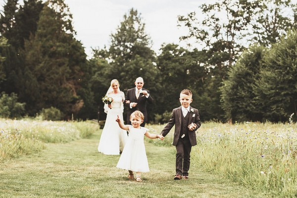 Flower girl and pageboy walking in front of bride