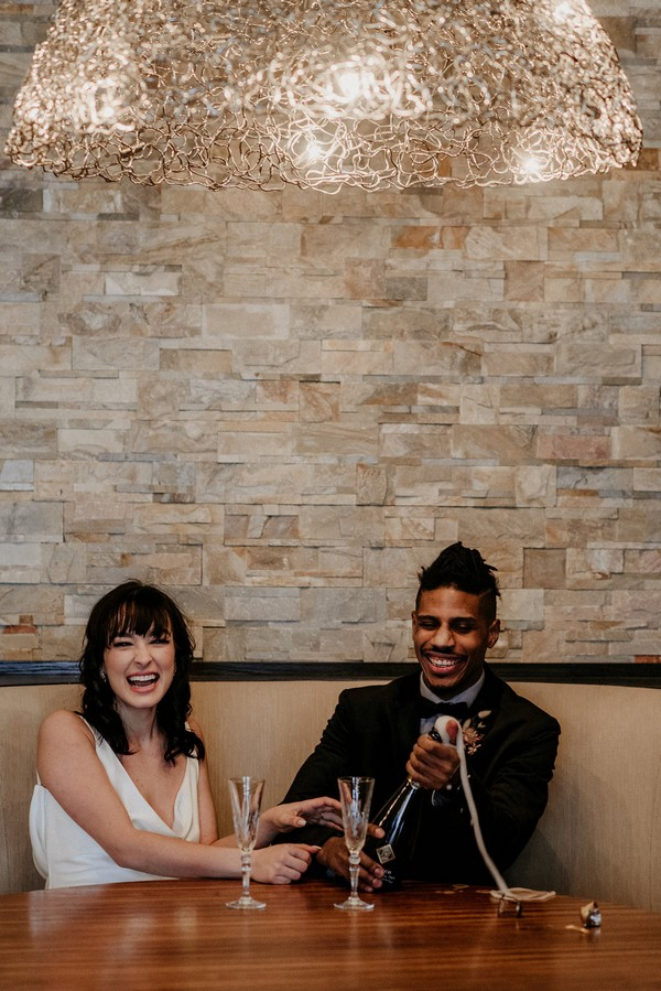 Bride and groom laughing as groom opens bottle of champagne