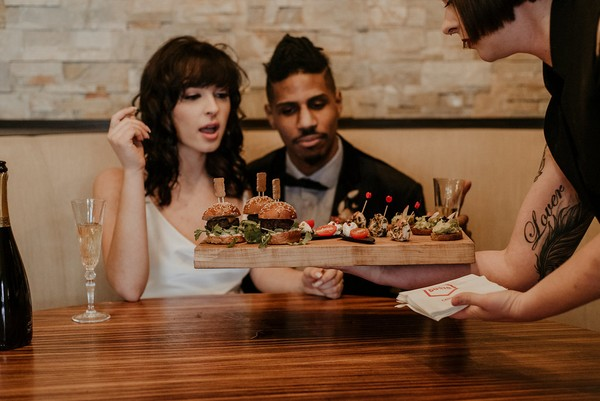 Bride and groom being served burger sliders