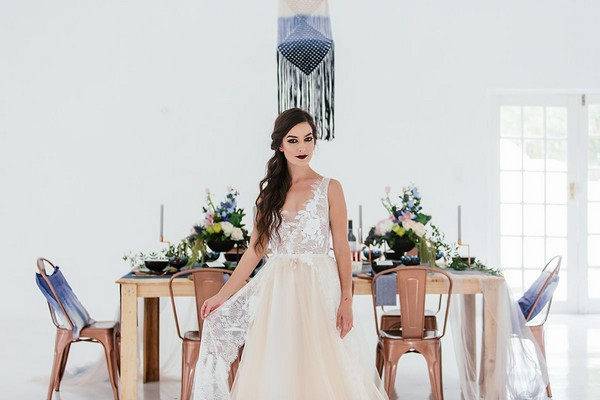 Bride standing in front of wedding table