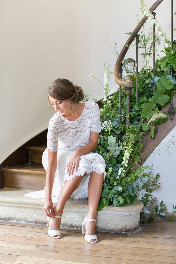 Bride sitting on stairs putting fastening shoe